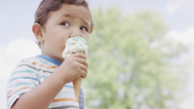 Toddler Eating Ice Cream A young Ethnic boy is eating ice cream from a cone in the park. It's a warm sunny day ice cream stock videos & royalty-free footage