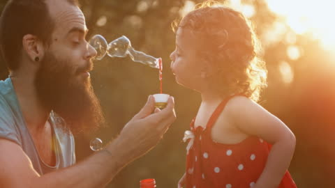 SLO MO Toddler girl blows bubbles into father's face in the setting sun Slow motion medium handheld shot of a little toddler girl in a red dress blowing bubbles into her dad's face outside in the setting sun. Shot in Slovenia. enjoyment stock videos & royalty-free footage