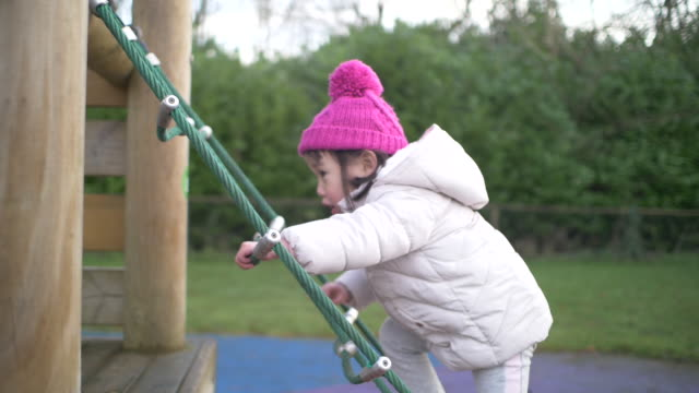 toddler girl climbing rope steps in witer playground video