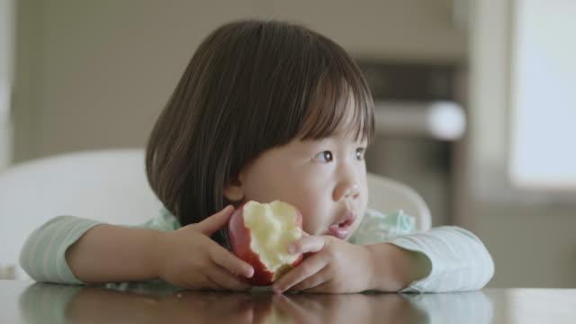 家庭の台所でリンゴを食べる幼児の女の子 - おやつ点の映像素材/bロール
