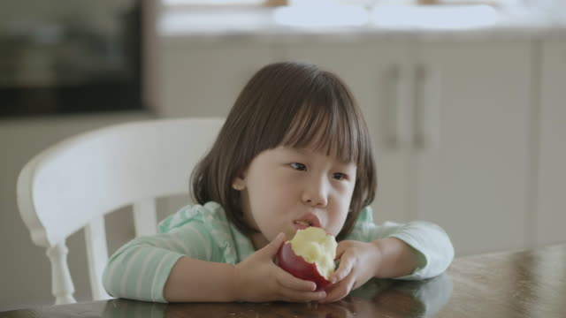 toddler girl eating apple at home kitchen hand hold shoot toddler girl sitting on  chair and eating apple by herself apple fruit stock videos & royalty-free footage
