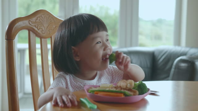 vídeos de stock e filmes b-roll de toddler girl eating broccoli at home - vegetables