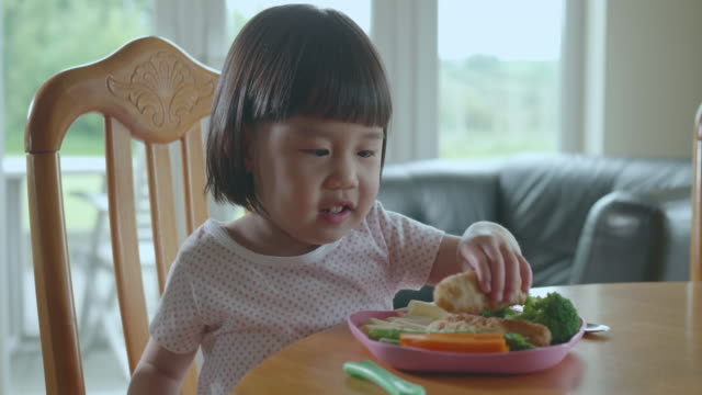 bambina che mangia goujons di pesce a casa - bambino piccolo video stock e b–roll