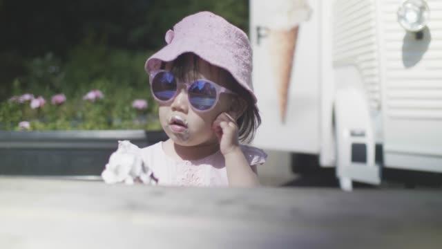 toddler girl eating ice cream on summer park