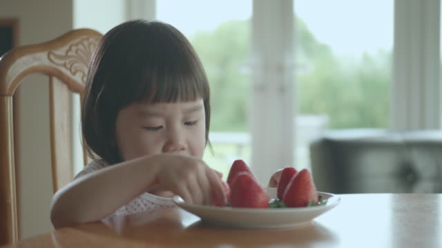 自宅でイチゴを食べる幼児の女の子 - おやつ点の映像素材/bロール