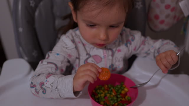 Toddler girl eating vegetable on her own