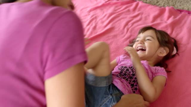 bambino piccolo ragazza riceve tickled da mamma - fare il solletico video stock e b–roll