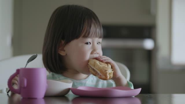 toddler girl having breakfast at home kitchen video