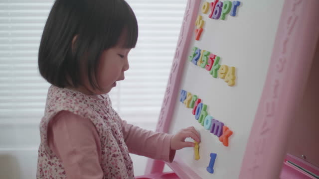 toddler girl leaning alphabet on white board at home