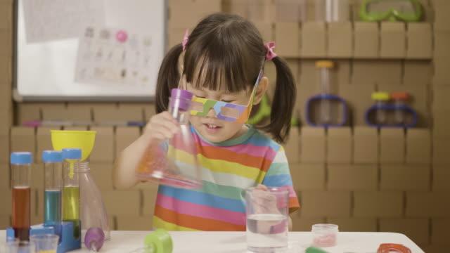 småbarn flicka spela vetenskap experiment färg blandning - förskoleelev bildbanksvideor och videomaterial från bakom kulisserna