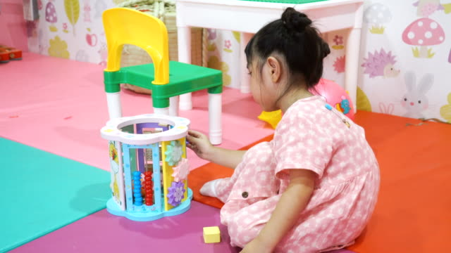 Toddler girl playing puzzle in toy room Toddler girl playing puzzle in toy room playroom stock videos & royalty-free footage
