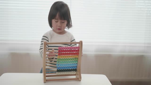 småbarn flicka leker med abacus hemma - abakus bildbanksvideor och videomaterial från bakom kulisserna