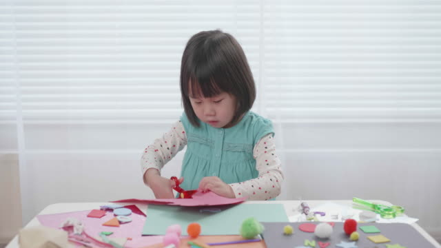 toddler girl practice making Origami at home against white background video