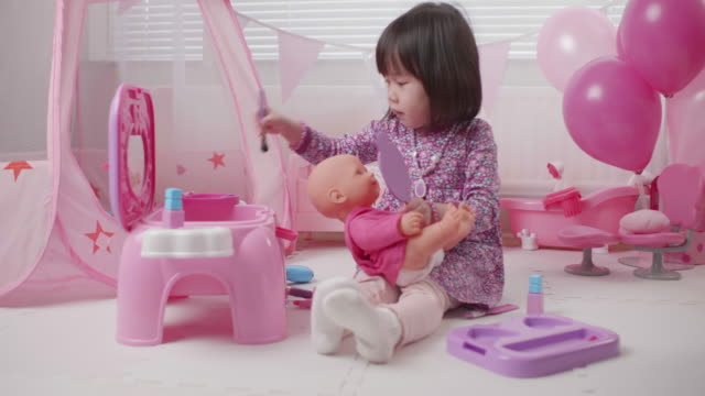 toddler girl pretend play baby care role at home against window background