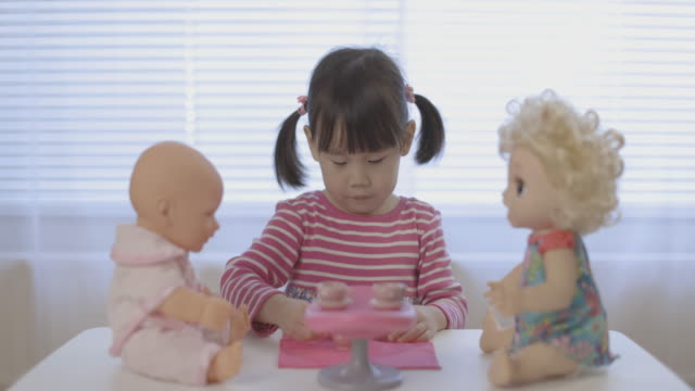 toddler girl pretend play baby care role at home against window background video