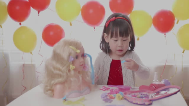 toddler girl pretend play hair styling against window background video