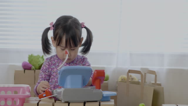 toddler girl pretend playing as shopkeeper on carton block table video