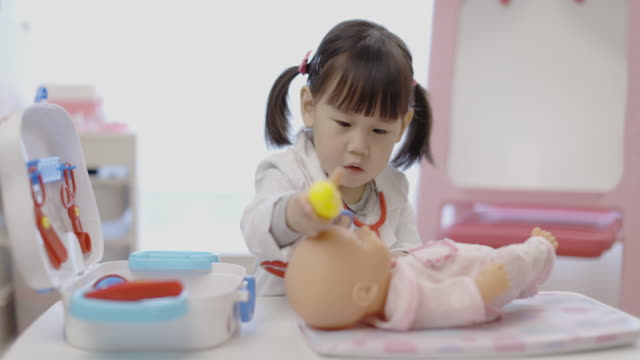 toddler girl pretend playing doctor looking after patient