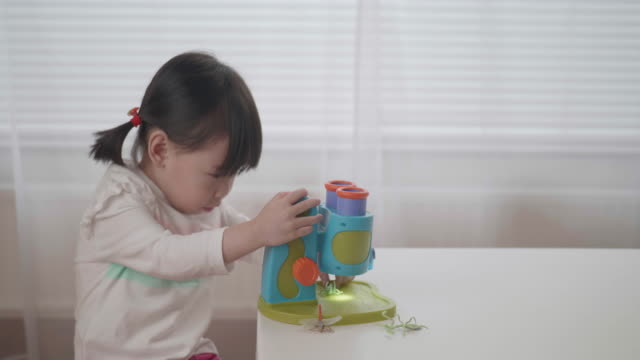 toddler girl pretend playing microscope at home video