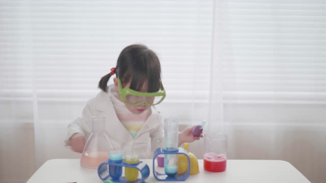 toddler girl pretend playing scientific research game at home video