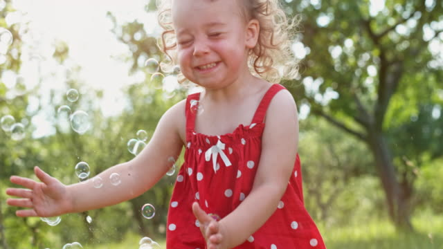 SLO MO Toddler girl running amongst soap bubbles in an orchard