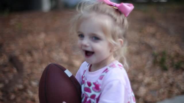 vídeos de stock e filmes b-roll de a toddler girl runs around her yard with a football. - criança pequena