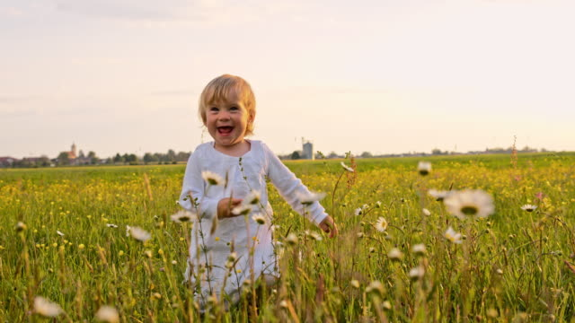 SLO MO Toddler girl taking first steps in the grass video