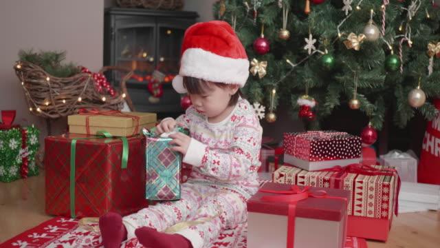 toddler girl unpacking Christmas gift box beside Christmas tree at home video