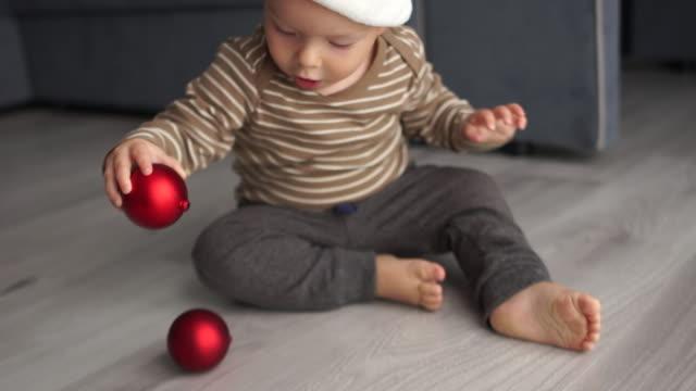 サンタのフリース帽子をかぶった幼児は、赤いクリスマスボールで遊んでいます。メリークリスマスとハッピーニューイヤー - サンタの帽子点の映像素材/bロール