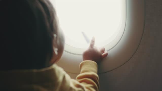 Toddler is watching panorama through window airplane