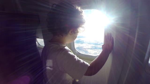 Niño está viendo panorama a través de la ventana de avión - vídeo