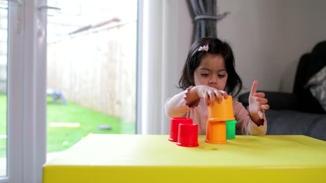 Toddler Playing With Plastic Stacking Cups
