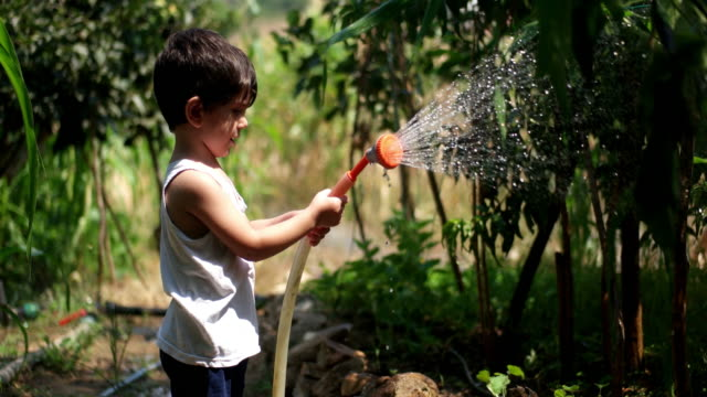 il bambino gioca con il tubo dell'acqua all'aperto durante l'estate - giardino pubblico giardino video stock e b–roll