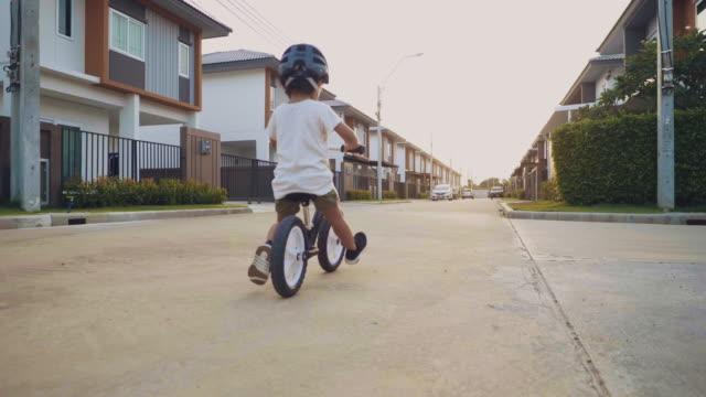 toddler riding balance bike. - neonati maschi video stock e b–roll