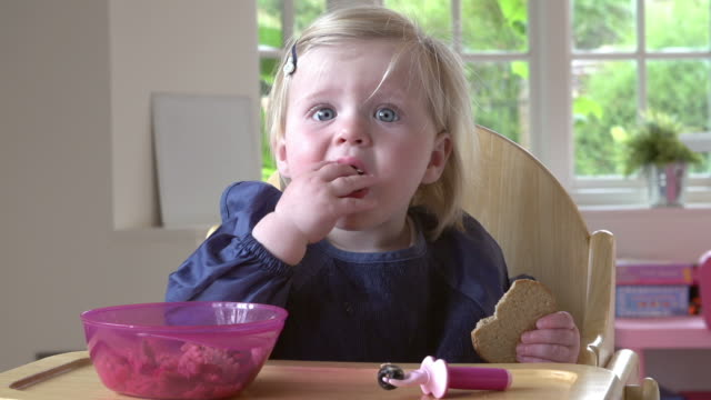 Toddler Sitting In High Chair Eating Food Young girl sitting in high chair eating food and making a mess.Shot on Sony FS700 at a frame rate of 25fps fork stock videos & royalty-free footage