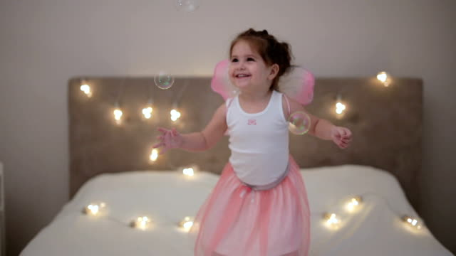 Toddler with fairy wings playing in the bedroom.