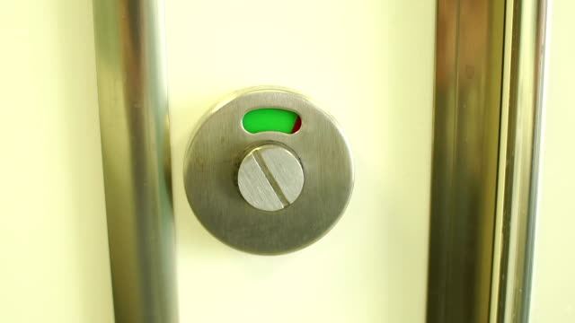 A toilet door lock with a red closed sign switches to a green open sign. Close-up of a toilet door lock with a red closed sign switches to a green open sign. Slow motion. bathroom stock videos & royalty-free footage