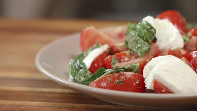 tomaten-basilikum-salat mit in scheiben geschnittenen mozzarella-käse - vegetarisches gericht stock-videos und b-roll-filmmaterial