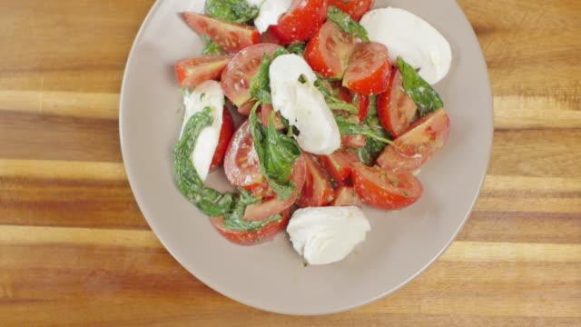 スライスしたモッツァレラ チーズ トマト バジルのサラダ - テーブル 無人のビデオ点の映像素材/bロール