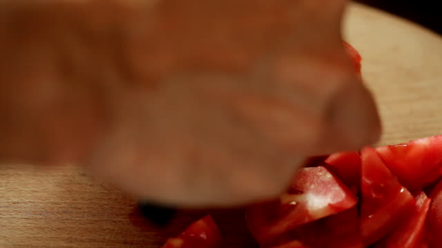 Tomato cutting HD video; chief cuts tomato into slices on kitchen plank using ceramic cutting knife; closeup; tomato salad stock videos & royalty-free footage