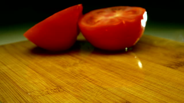 Tomato halves fall on wooden cutting board. Super slow motion close up video video