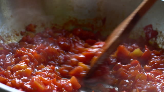 vídeos de stock e filmes b-roll de tomato sauce.  close up. slow motion. boiling tomato sauce made from chopped fresh ripe tomatoes. cook adds black pepper and stirs boiling sauce with ð° wooden spatula. italian cuisine. - sauce tomatoes