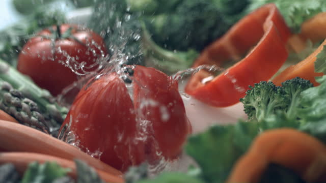 Tomato splashing into water, slow motion video