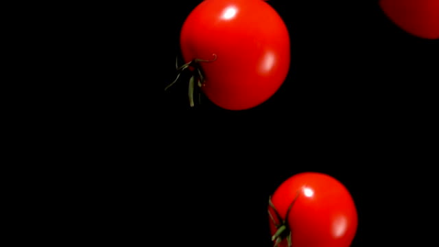 Tomatoes are falling down on on a black background - video