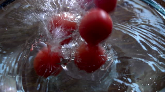 Tomatoes falling into water, Slow motion video