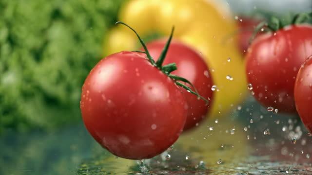 SLO MO Tomatoes falling on a table