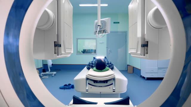vídeos de stock e filmes b-roll de tomograph panels move around a person. patient on magnetic resonance imaging, medical examination. - instrumento para diagnóstico