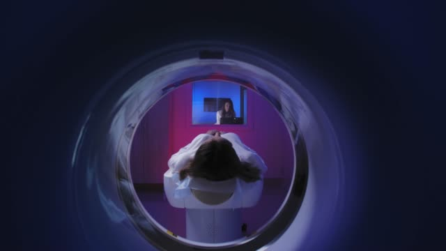 Tomograph. The patient on the CT scan. View through the tomograph from behind. Tomograph. The patient on the CT scan. View through the tomograph from behind radiologist stock videos & royalty-free footage