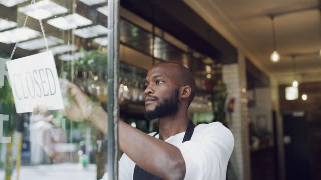 Tomorrow is another day to try again 4k video footage of a young man hanging a closed sign on the window of a cafe bankruptcy stock videos & royalty-free footage