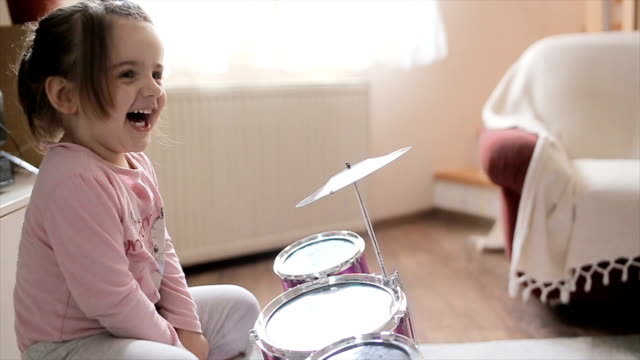 Too cute girls playing drums at home